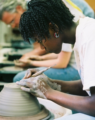 A student works at the ceramic wheel in Professor Mullinix's class