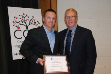 Head Football Coach Drew Cronic is pictured accepting the Partner of the Year Award from Dr. Brian Hightower, superintendent of the Cherokee County School District.