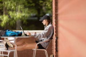 A female college student sits at an outdoor table, working on her laptop.