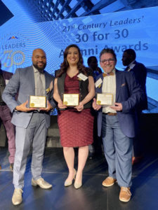 Three of Reinhardt's alumni pose with awards