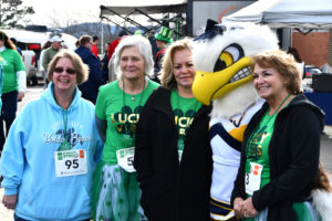 Three race participants pose with the Lady Soar eagle mascot