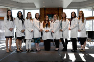 Reinhardt's fifth cohort of nursing students standing in a line on stage
