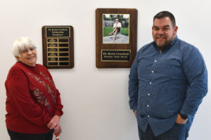Barbara and Todd Crawford stand with Dr. Kevin Crawford's plaques.