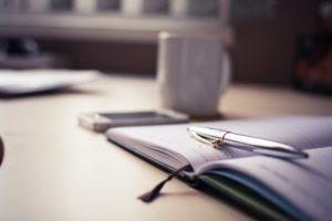 silver-click-pen-on-open-book-210660