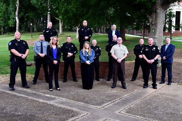 Students of Reinhard'ts ExCL program stand sociall distanced in the Echo Garden wearing law enforcement uniforms.