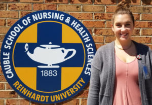 A student stands next to Cauble School of Nursing sign
